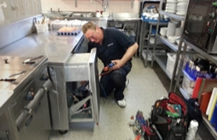 Man fixing a cooker in a Modern kitchen