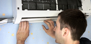 man fixing Air con unit on wall with blue and stars wall paper