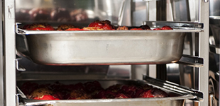 Stainless steel trays of food in commercial kitchen